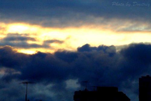 Солнце сквозь тучи над крышами домов